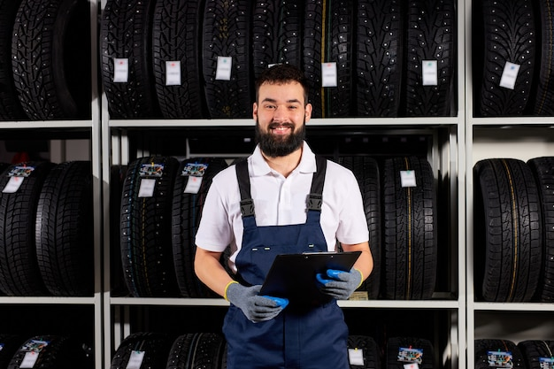 Male mechanic with clipboard near tires in automobile service center looking at camera and smiling, in blue uniform