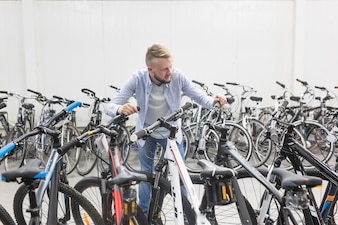 Male mechanic with different types of bicycles in shop