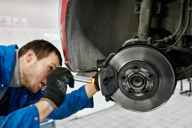 Мужчина-механик с открытым ртом в черных перчатках и синей униформе, держит фонарик и внимательно осматривает шины или тормозные колодки поднятого автомобиля в автомастерской. автосервис и концепция техника
