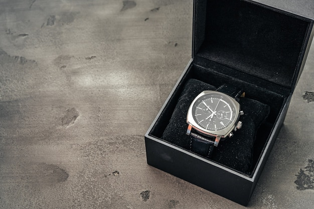 Male mechanical watch on dark concrete surface close up