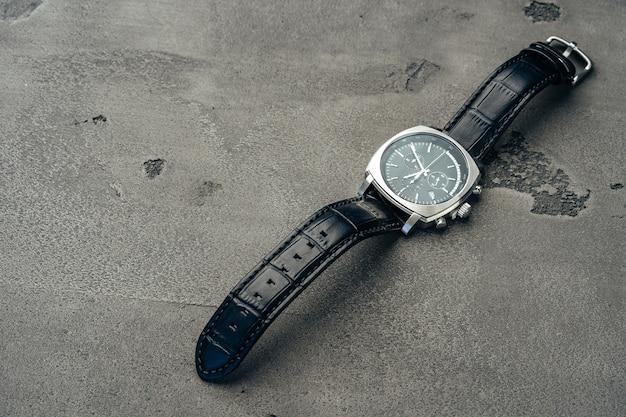 Male mechanical watch on dark concrete surface