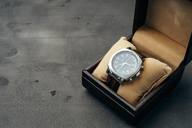 Male mechanical watch on dark concrete