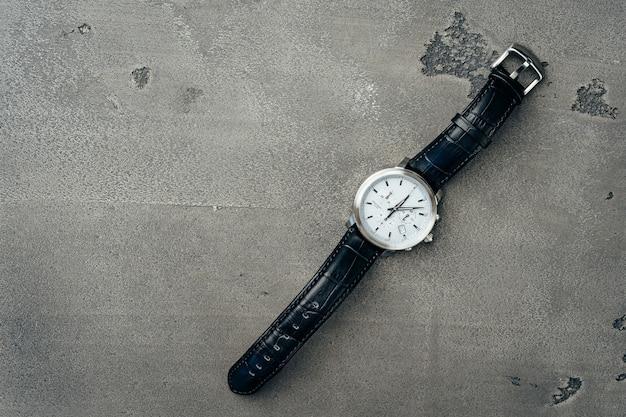 暗いコンクリート表面の男性の機械式時計のクローズアップ