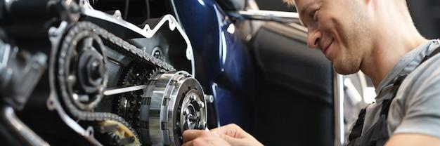 Male mechanik repair motorcycle in special service portrait