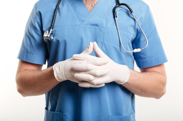 Male medical doctor or nurse wearing surgical gloves and stethoscope