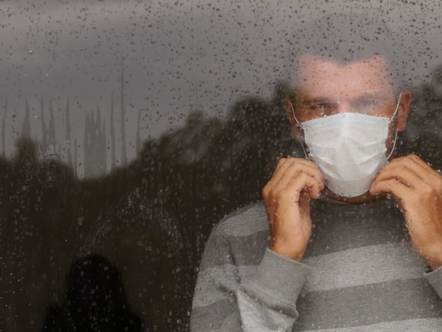 Male in medical mask looking through window in a sad rainy day. copy space. covid-19 concept