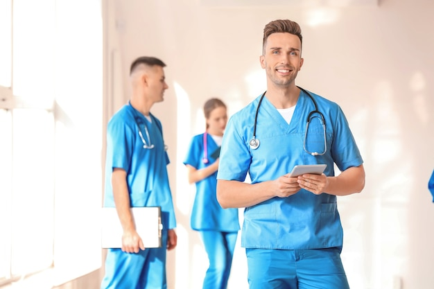 Male medical student with tablet computer in hall of clinic