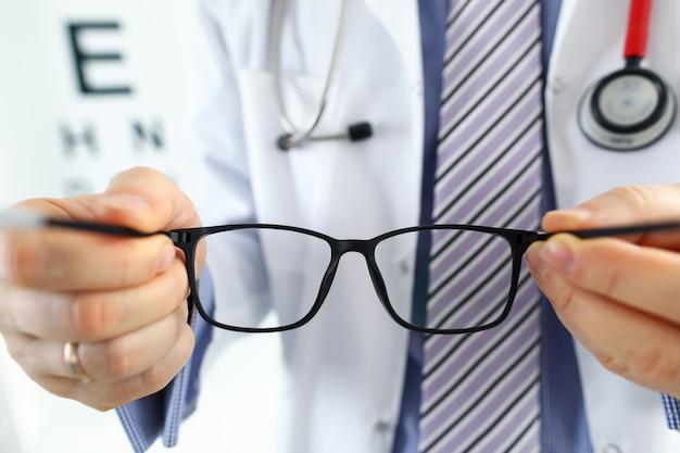 男性医学博士の手が患者に黒い眼鏡のペアを与えます。視力検査と矯正優れたビジョンレーザー手術代替ドライバー健康証明書検査コンセプト