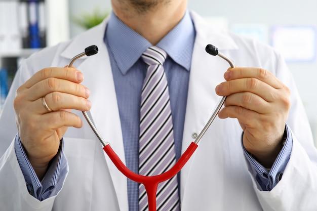 Мужские руки доктора медицины держат и кладут на стетоскоп перед его крупным планом комода. здоровое сердце, питание и образ жизни, врач готов осмотреть пациента, физические и профилактика заболеваний