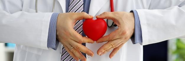 Мужской доктор медицины руки держа и охватывающих красный игрушка сердце крупным планом. кардио терапевт студент образования врач сделать сердечную физическую частоту сердечных сокращений концепции аритмии