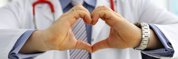 Male medicine doctor hands showing heart shape closeup. medical help prophylaxis or insurance concept. cardiology care health protection and prevention healthy heart concept