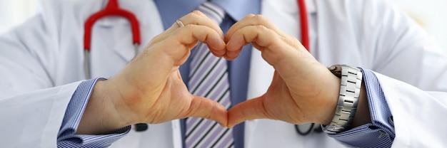 Мужской доктор медицины руки, показывая форму сердца
