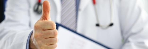 ドキュメントパッドを手に持った男性医師は、親指で[ok]または承認のサインを表示します。高レベルで質の高い医療サービス最高の治療健康な患者のコンセプト。満足している幸せなインターン