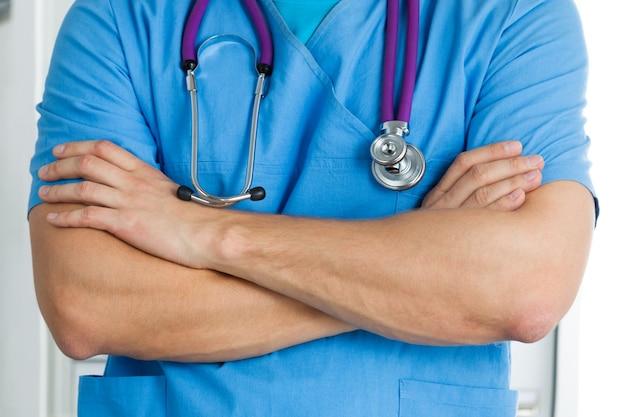 Врач медицины мужского пола, стоя с его руками, скрещенными на груди, готов к работе. здравоохранение и медицинская концепция.