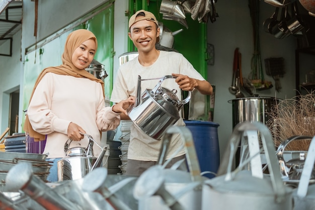 Торговец-мужчина демонстрирует азиатской женщине традиционные чайники в магазине бытовой техники