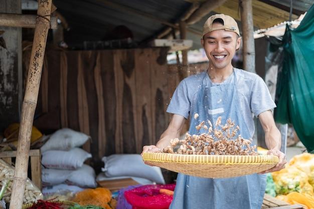 Торговцы-мужчины в фартуках с плетеными бамбуковыми подносами чистят куркуму в овощном киоске