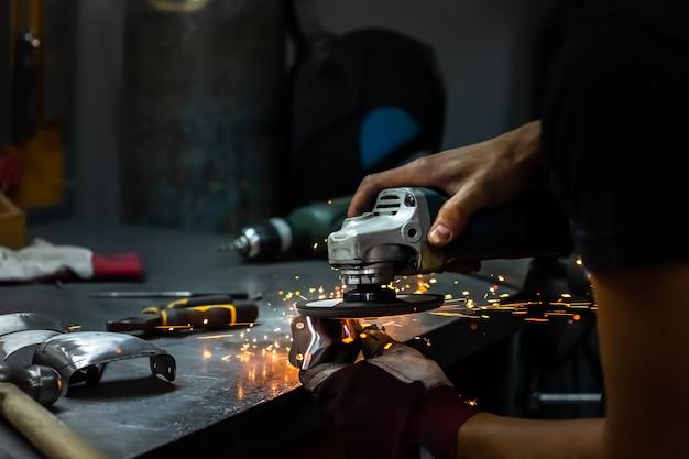 Мужчина-слесарь полирует и дорабатывает средневековый доспех. руки человека обработки металлических частей оборудования в мастерской с угловой шлифовальной машиной.