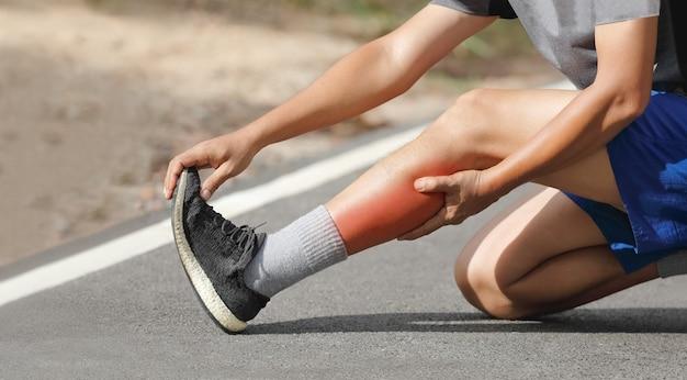 ジョギング中にけいれんを起こしている中年男性。ふくらはぎを止めてマッサージする
