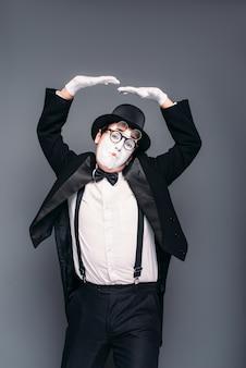 Мужчина-актер пантомимы весело подражает выполнению. пантомима в костюме, перчатках, очках, маске для макияжа и шляпе.