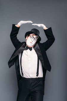 Male mime actor fun mimic performing. pantomime in suit, gloves, glasses, make-up mask and hat.