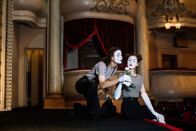 Male mime artist giving white rose to female mime sitting on stage