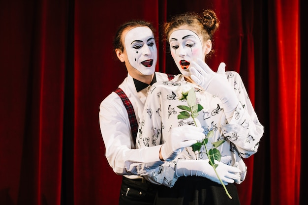 Male mime artist giving white rose to surprised female mime