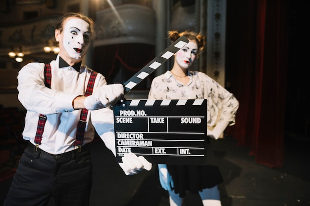 Male mime artist holding clapper in front of female mime artist