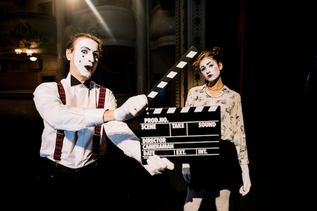 Male mime artist holding clapperboard in front of female mime artist