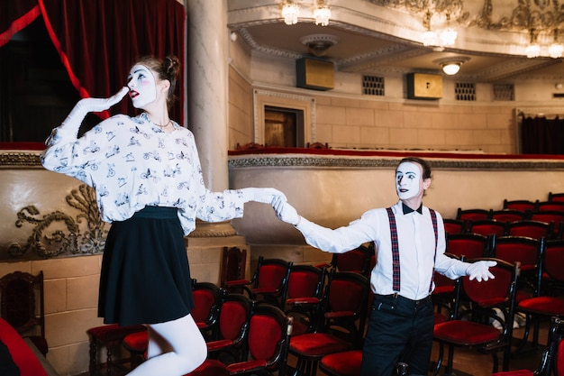 Male mime artist holding shy female mime's hand in auditorium