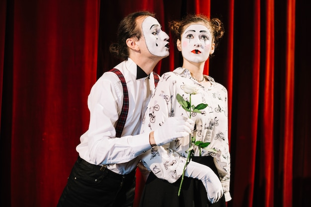Male mime artist holding white rose in front of female mime