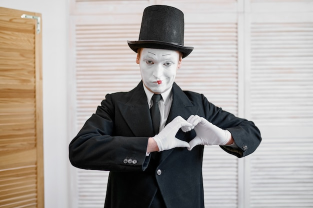 Male mime artist, love heart gesture, parody