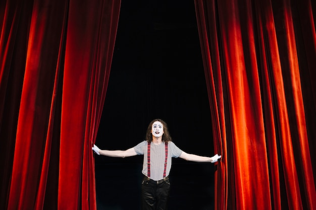 Male mime artist performing on stage near red curtain
