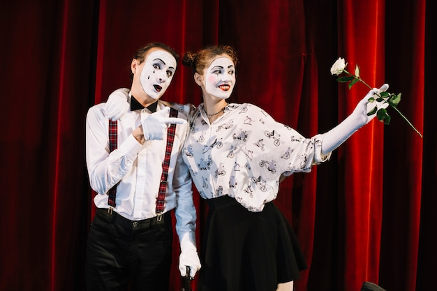 Male mime artist pointing toward female mime holding white rose