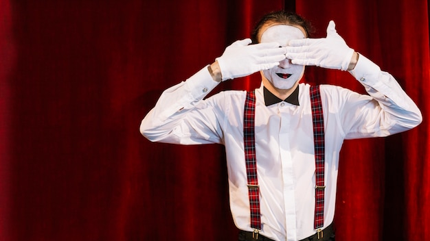Male mime artist standing in front of curtain covering his eyes with hands