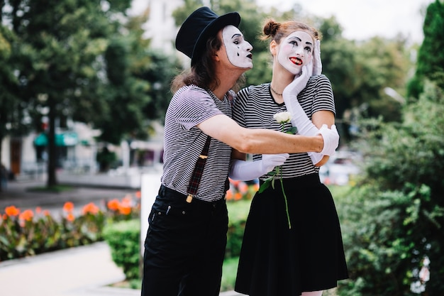 Male mime embracing happy female mime in park