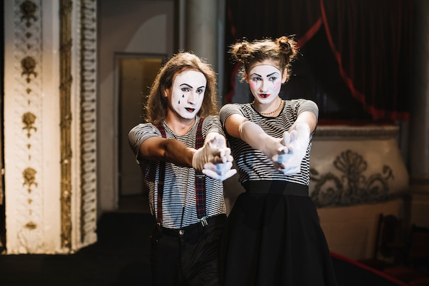 Male mime and female mime making hand gun gesture