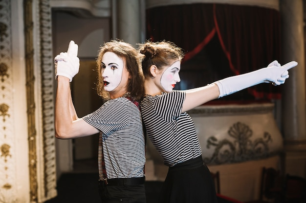 Male mime and female mime standing back to back making hand gun gesture