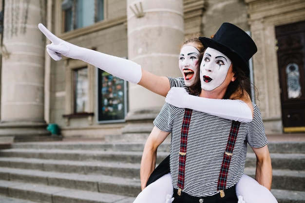 Male mime giving piggyback ride to female mime pointing at something