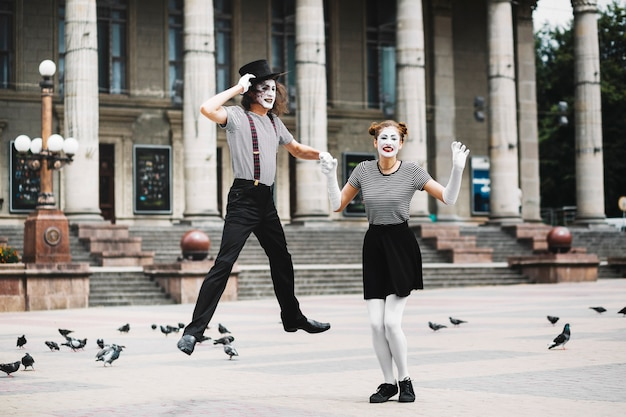 Male mime holding female mime's hand jumping in front of building