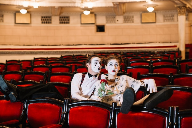 Male mime holding red rose sitting with bored female mime on chair in auditorium