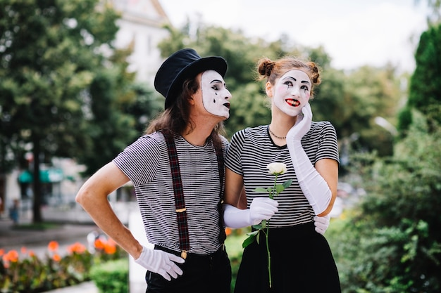 Male mime looking at happy female mime in park
