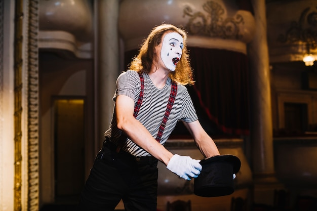 Male mime performing on stage holding hat
