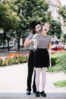 Male mime scaring female mime in park