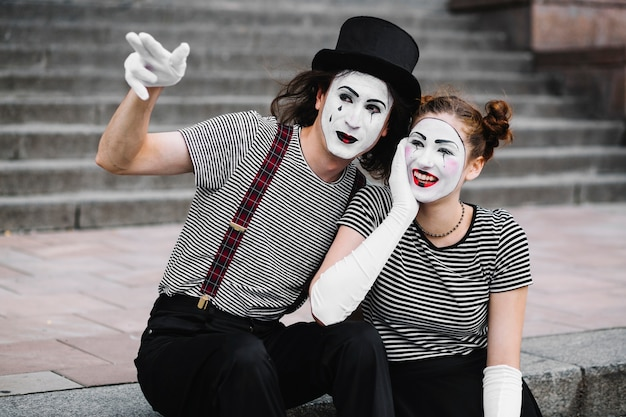 Male mime showing something to happy female mime