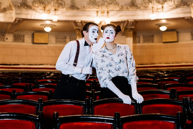Male mime whispering in female mime's ear standing among chair