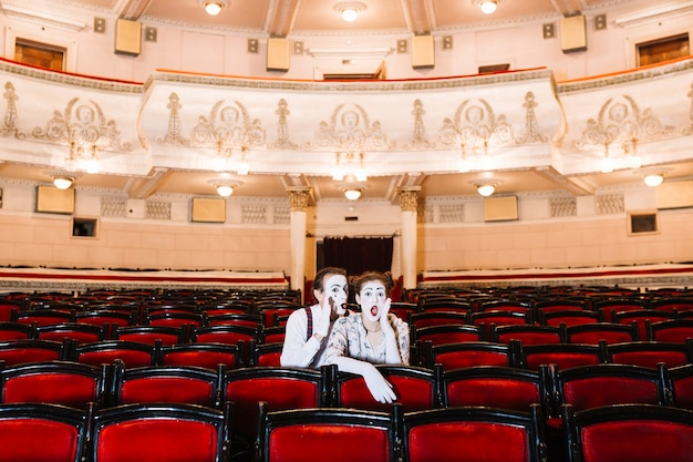Male mime whispering in shocked female mime's ear sitting on chair in auditorium