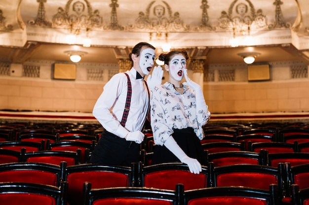 Male mime whispering in shocked female mime's ear standing among chair in auditorium