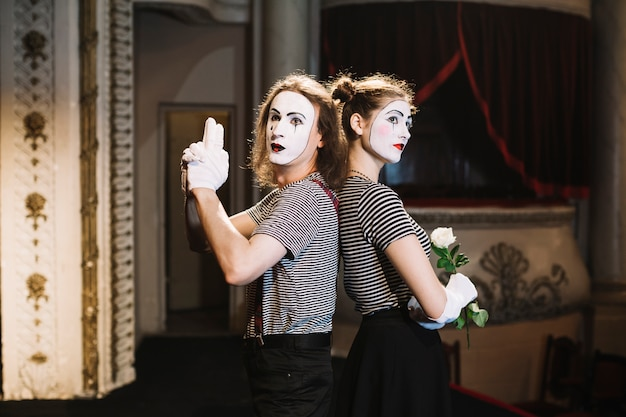 Male mime with hand gun gesture and female mime holding rose standing back to back