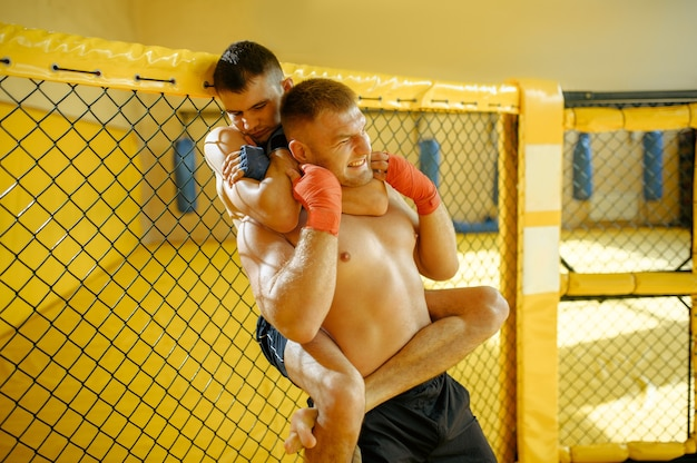Male mma fighter performs painful choke hold to his opponent in a cage in gym.