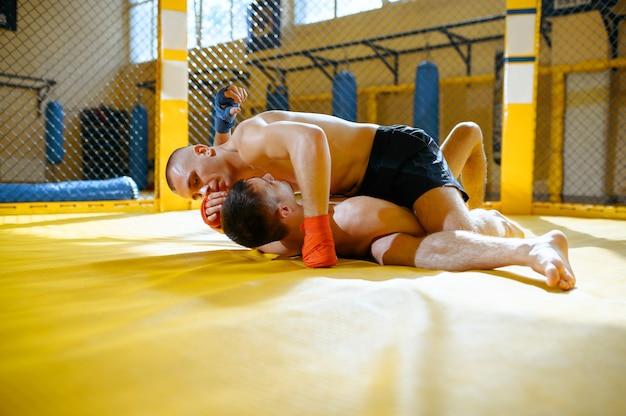 남성 mma 전투기는 체육관의 새장에서 상대방에게 고통스러운 홀드를 수행합니다.